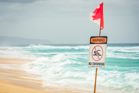 A warning sign indicating no swimming due to large, dangerous ocean waves.