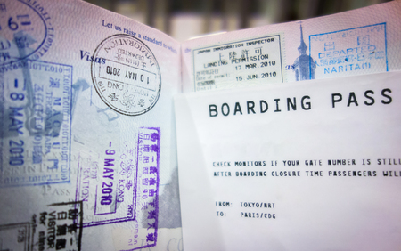 Airplane boarding pass and heavily stamped passport indicating frequent travel. Stock Photo