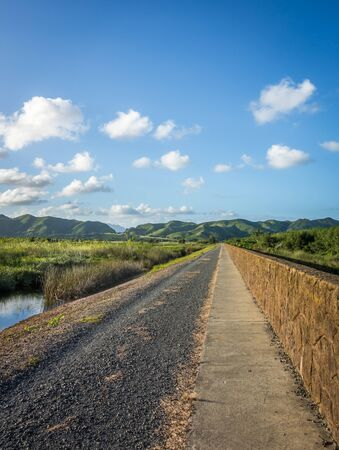 A long path extending as far as the eye can see, into lush green mountains below blue skies on a beautiful sunny day in Hawaii.