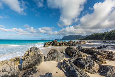 Large rocks and beautiful emerald green waters of Waimanalo on a sunny day on the island of Oahu, Hawaii, with the forest and mountains visible in the background.