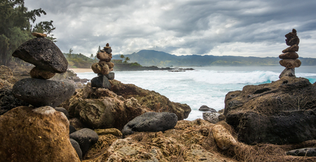 Stacked rocks, giant waves, and lush green mountains on a cloudy day on the North Shore of Oahu, Hawaii. Banco de Imagens