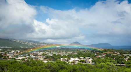A bright and vibrant ultra-low Hawaiian rainbow over the lush green vegetation of a residential neighborhood of Honolulu.
