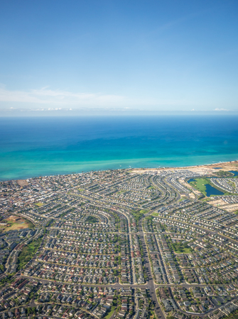 An aerial shot of Hawaiian suburbs, showing rows and rows of houses located near the gorgeous blue waters of Eva Beach on Oahus leeward side. Stok Fotoğraf