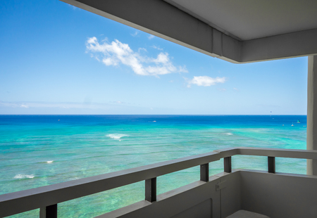 Gentle waves rolling in on the beautiful emerald green waters of Waikiki, as seen from a high-rise balcony.