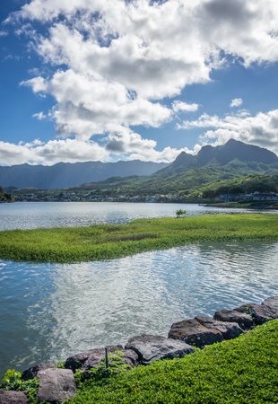 Blue skies, lush green mountains, and the calm waters of Enchanted Lakes in the town of Kailua on Oahu, Hawaii.