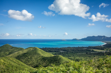 The lush green mountains and beautiful turquoise ocean water of Waimanalo Bay, Hawaii, as seen from the top of the Lanikai Pillbox hike.