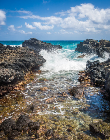 A beautiful turquoise ocean wave crashing through a narrow rocky inlet near Sandy Beach on the island of Oahu, Hawaii.