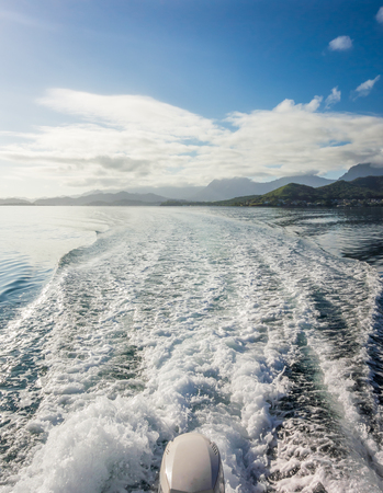 The waves and splashing water viewed from the back of a boat speeding across the blue water of Kaneohe Bay on Oahu, Hawaii.