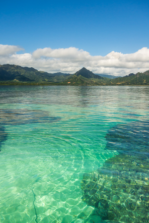 The crystal clear emerald green waters, beautiful coral reefs, and lush green mountains of Kaneohe Bay on the island of Oahu, Hawaii. Stok Fotoğraf