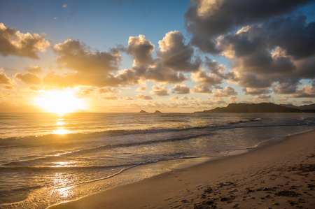 A gorgeous golden sunrise turns into blue skies over Kailua Bay on the island of Oahu, Hawaii.
