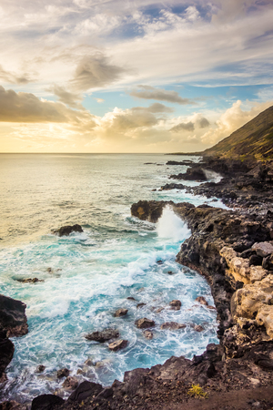 Waves crash into the rocky coastline of west Oahu along the way to Kaena Point, warmed by the sunlight of a golden Hawaiian sunset. Stok Fotoğraf