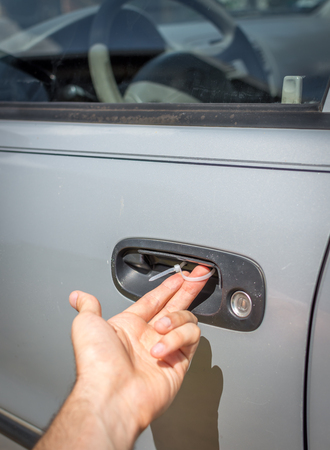 A makeshift car door handle fix using a simple zip tie looped through drilled holes. Stock Photo