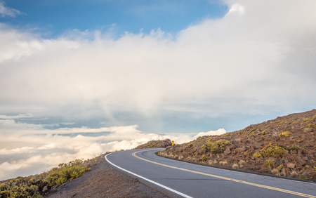 jetsetter: A winding mountain road high above the clouds, on the way to Haleakala on Maui, Hawaii. Stock Photo