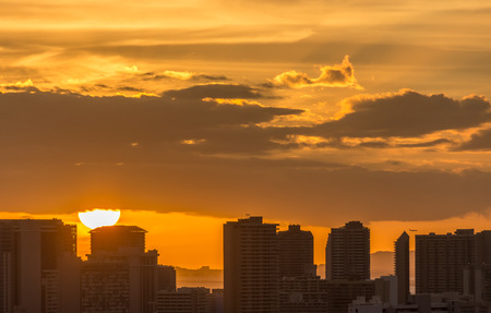 A golden orange sunset over the urban Honolulu skyline.