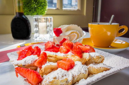 Dutch mini pancakes known as Poffertjes, with strawberries, powdered sugar, and whipped cream, with a side of coffee at a Dutch cafe. Stok Fotoğraf