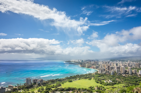 A rainstorm giving way to beautiful blue skies over the city of Honolulu and the beautiful turquoise water of Waikiki, as seen from the top of Diamond Head summit.