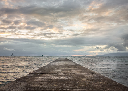 Waikiki pier stretching out toward the ocean where sail boats cruise along the cloudy evening horizon.