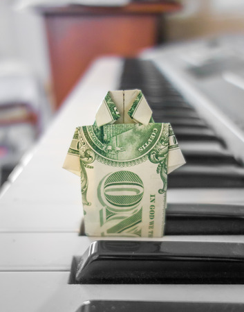 A crisp US dollar bill folded into collared shirt origami, standing between piano keys.