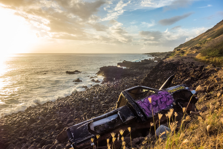 An abandoned truck discarded on a rocky coast line, with an ocean sunset in the background.