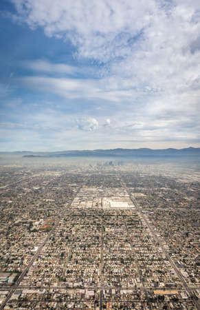A sweeping aerial shot of Los Angeles showing symmetrical rows of buildings and roads leading into downtown, with mountains and smog visible in the background.
