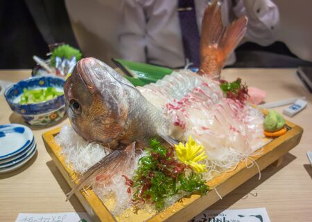 A decorated plate of red snapper freshly prepared as Japanese sashimi (raw fish) with a side of wasabi and seaweed.