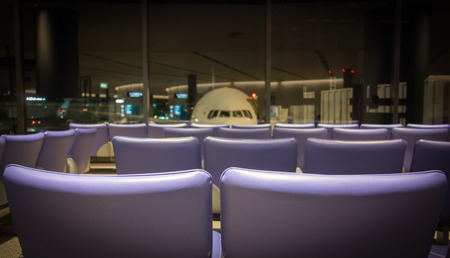 Rows of empty seating in an airport waiting area, with a grounded airplane visible in the background.