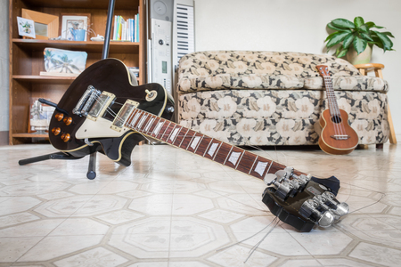 A broken black electric guitar that fell off its stand, hit the ground, and snapped at the neck. Guitar strings frayed. Other musical instruments (ukulele, electric piano) visible in background.