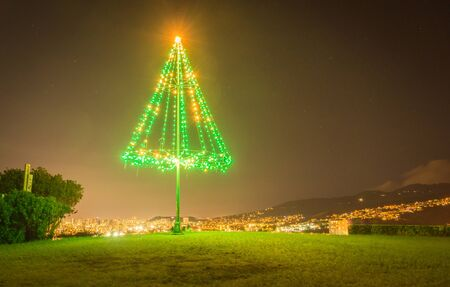 A large, outdoor, metal Christmas tree brightly illuminated with green and gold Christmas lights, at night time on top of a hill with the Honolulu skyline visible in the background. Stok Fotoğraf