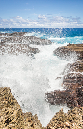 Large waves smashing through a sharp, rocky inlet on the coastline of the eastern side Oahu, Hawaii. Stok Fotoğraf