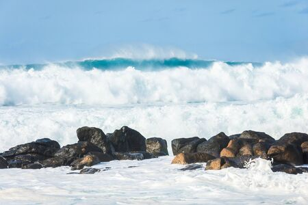 Giant blue waves crashing into large rocks near the Banzai Pipeline on the North Shore of Oahu, Hawaii.