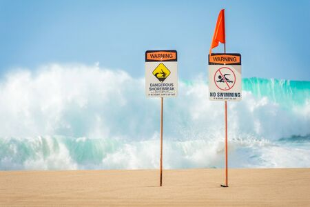 Warning signs indicating no swimming allowed due to huge waves and dangerous shorebreak near the Banzai Pipeline on the North Shore of Oahu, Hawaii.