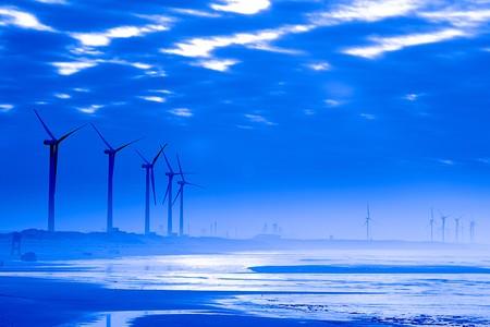 Blauwe hemel, steen, windmolen reflectie op het strand  Stockfoto