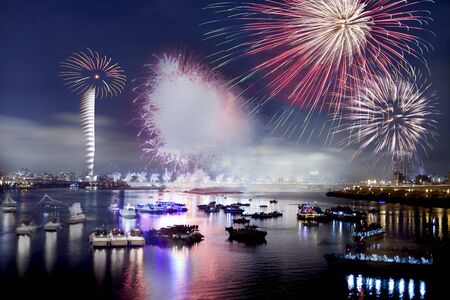 Fireworks firing up into the sky with a boat on a river below them, with a reflection on the water  photo