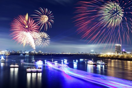 Fireworks firing up into the sky with a boat on a river below them, with a reflection on the water  Stock Photo