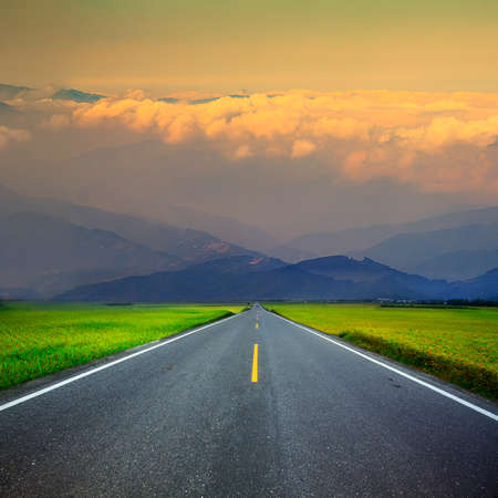 no lines: Asphalt road through the green field and clouds on blue sky in summer day