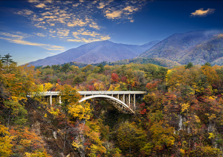 The autumn colors of Naruko Gorge in Japan and nice blue and cloud background Archivio Fotografico