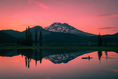 Kayaker and mountain reflections at beautiful lake during vibrant sunset in Oregon Stockfoto