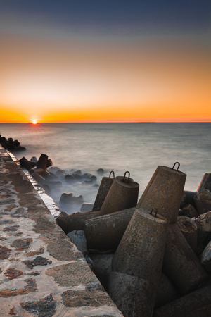 Beautiful sunset on the background of the breakwater in the Baltic