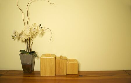 An orchid with 3 small containers sitting on the table Stock Photo