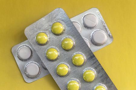 Pastillas redondas amarillas en un paquete sobre un fondo amarillo, cerrar Foto de archivo