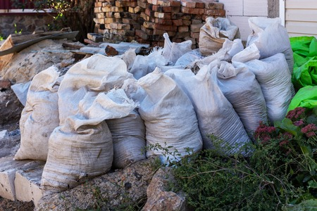 white bags with construction debris on street