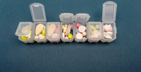 plastic organizer for tablets. tablets are red, white, round. close-up