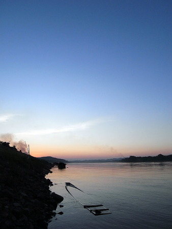 landscape riverside: Sinking boat in the river at sunset.