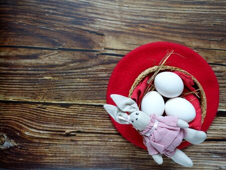 festive Easter layout of three eggs in a straw basket on a colored background