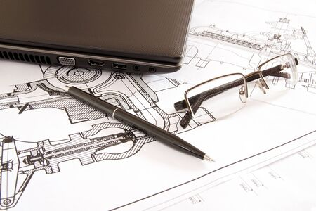 glasses and pen lying next to a laptop Stock Photo