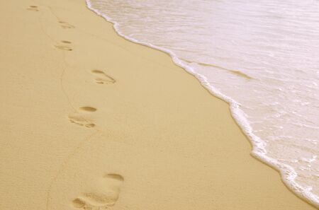 footprints on the sand near the surf line Stock Photo
