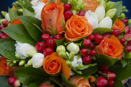 bouquet of orange and white roses decorated with berries with drops of dew