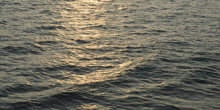 rays of the setting sun reflected on the waves of the Indian Ocean