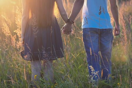 couple holding hands outdoors, meeting sunset