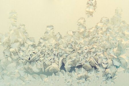 Beautiful frosty patterns on the window in the winter